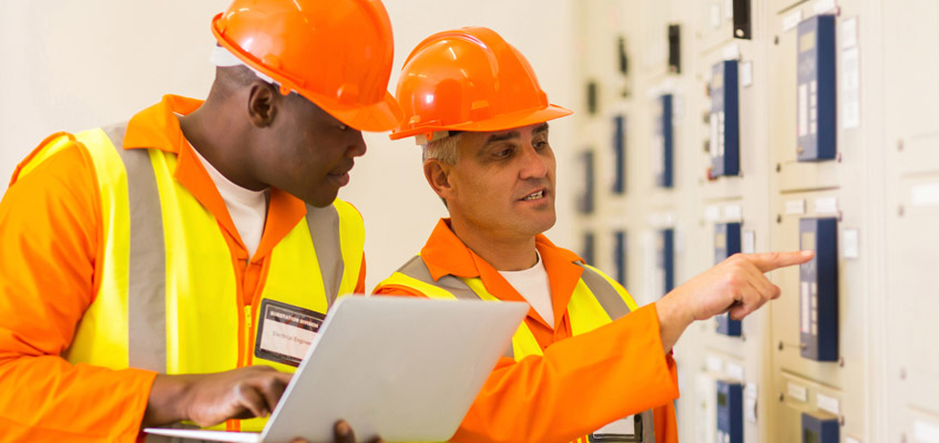 Two electricians inspecting industrial electrical substations