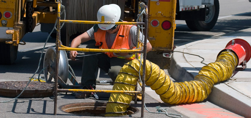 Worker with safety vest feeding underground cable into manhole